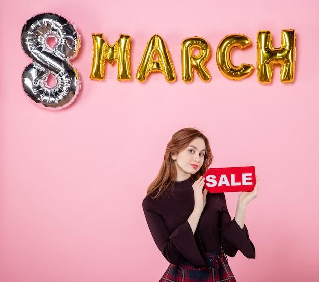 Vooraanzicht jonge vrouw met rood verkoopnaambordje op roze huwelijksfeest, vrouwendagcadeau, winkelvakantie