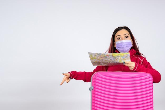Vooraanzicht jonge vrouw met roze zak in masker bedrijf kaart op witte muur vrouw kleur virus vakantie pandemie reis covid-