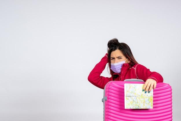Vooraanzicht jonge vrouw met roze zak in masker met kaart op witte muur kleur virus vakantiereis vrouw covid-