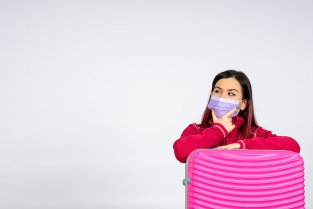 Vooraanzicht jonge vrouw met roze zak in masker op witte muur virus vakantie covid kleur pandemie vrouw