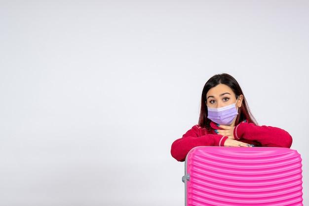Vooraanzicht jonge vrouw met roze zak in steriel masker op witte muur kleur virus vakantie covid pandemie reis vrouw