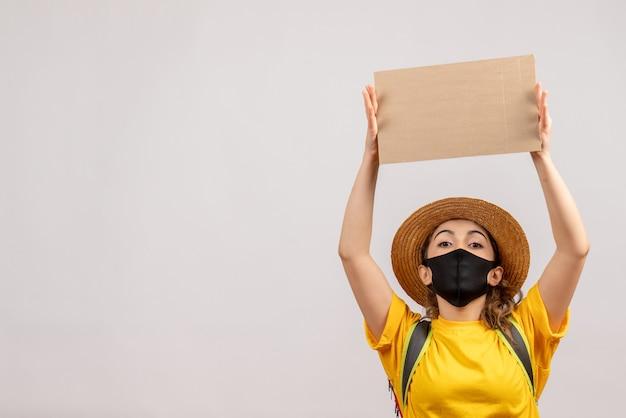 Vooraanzicht jonge vrouw met rugzak die een zwart masker draagt dat karton boven haar hoofd houdt