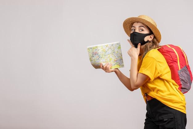 Vooraanzicht jonge vrouw met rugzak die kaart omhoog houdt en hand op haar kin legt