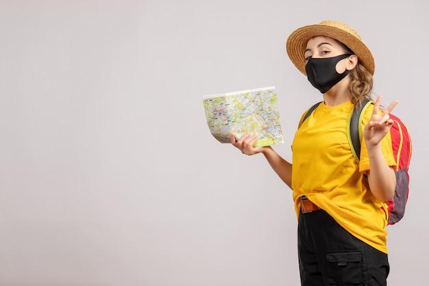 Vooraanzicht jonge vrouw met rugzak die kaart omhoog houdt en ok teken gebaart
