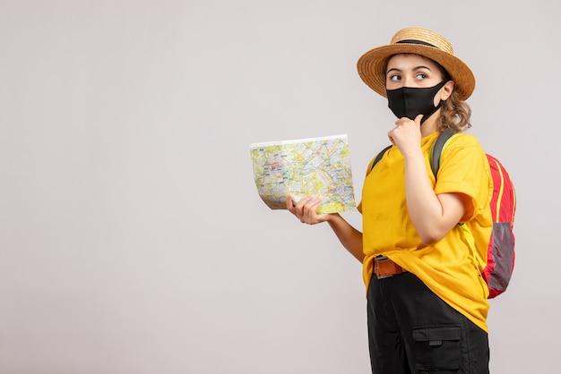 Vooraanzicht jonge vrouw met rugzak die kaart omhoog houdt