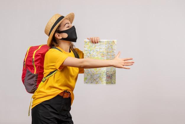 Vooraanzicht jonge vrouw met rugzak die kaart steunt en hand geeft