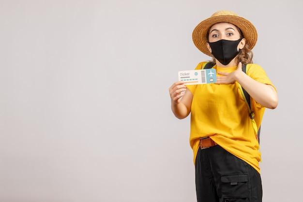 Vooraanzicht jonge vrouw met rugzak die zwart masker draagt dat reiskaartje houdt