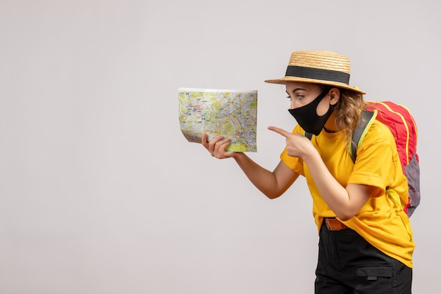 Vooraanzicht jonge vrouw met rugzak wijzend op map