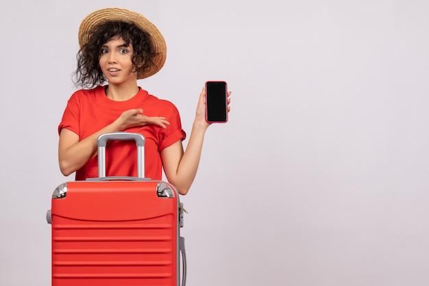 Vooraanzicht jonge vrouw met tas die zich voorbereidt op een reis met telefoon op een witte achtergrond zon reis vliegtuig toeristische vakantie kleur rust vlucht