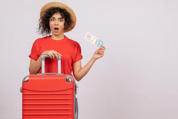 Vooraanzicht jonge vrouw met tas die zich voorbereidt op een reis met ticket op een witte achtergrond zon reis vliegtuig toeristische vakantie kleur rust vlucht
