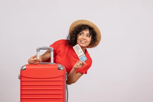 Vooraanzicht jonge vrouw met tas die zich voorbereidt op een reis met ticket op witte achtergrondkleur zon reis toeristische vakantie rust vlucht vliegtuig flight