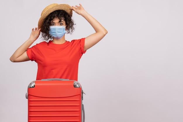 Vooraanzicht jonge vrouw met tas die zich voorbereidt op een reis op witte achtergrondkleur covid-reis toeristische vakantie pandemische zon virus