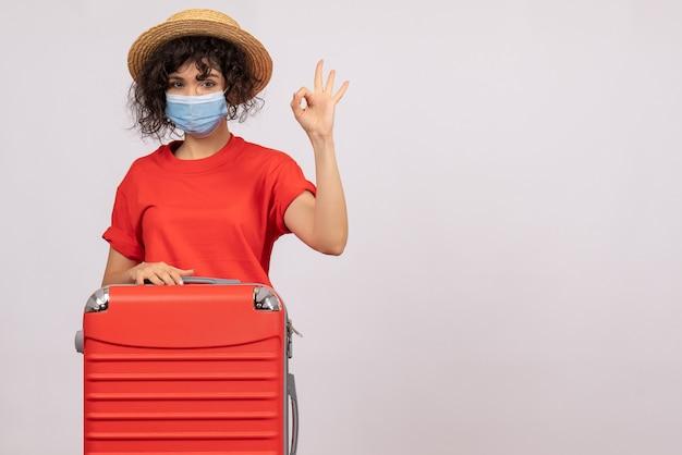 Vooraanzicht jonge vrouw met tas in masker op witte achtergrondkleur covid-vakantie pandemische zon reis toerist