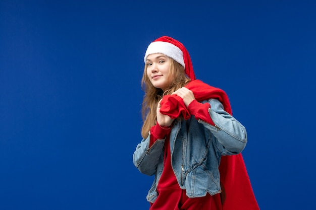 Vooraanzicht jonge vrouw met tas vol cadeautjes op de blauwe achtergrond emoties vakantie kerst