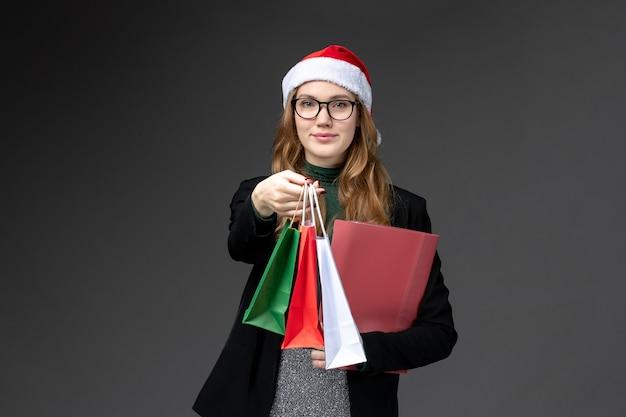 Vooraanzicht jonge vrouw met vakantie presenteert op donker bureau nieuwe jaar cadeau kerst