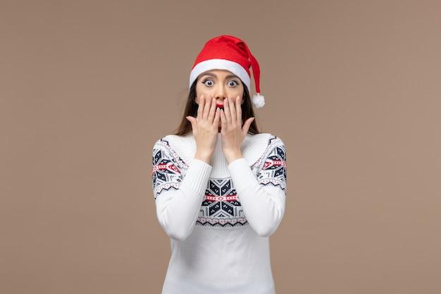Vooraanzicht jonge vrouw met verbaasde uitdrukking op bruine achtergrond nieuwjaar emoties kerstmis
