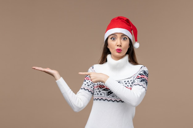 Vooraanzicht jonge vrouw met verbaasde uitdrukking op bruine achtergrond vakantie emotie kerst