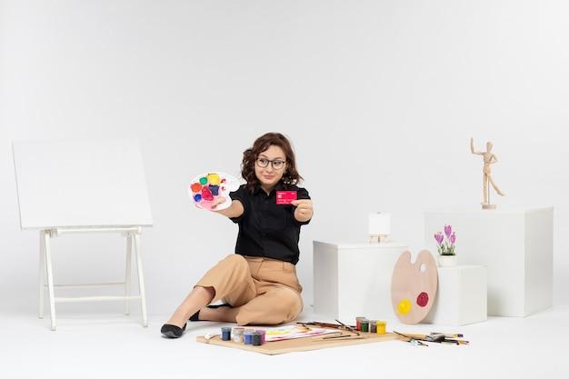 Vooraanzicht jonge vrouw met verf en bankkaart op witte achtergrond