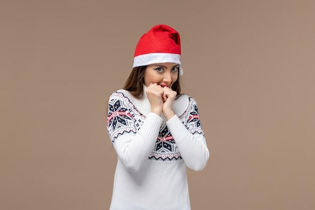 Vooraanzicht jonge vrouw met verlegen uitdrukking op bruine achtergrond kerst emotie nieuwjaar