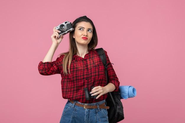 Vooraanzicht jonge vrouw met verrekijker en camera op roze achtergrond kleur vrouw mens