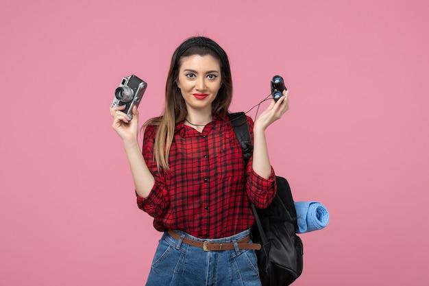 Vooraanzicht jonge vrouw met verrekijker en camera op roze achtergrond menselijke kleur vrouw