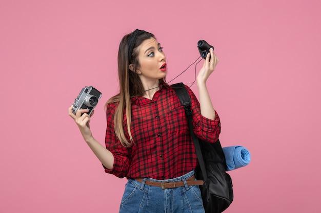 Vooraanzicht jonge vrouw met verrekijker en camera op roze achtergrond menselijke kleuren vrouw