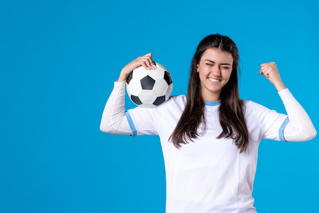 Vooraanzicht jonge vrouw met voetbal op blauwe muur