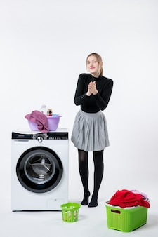 Vooraanzicht jonge vrouw met wasmachine en vuile kleren op witte muur