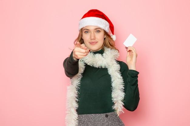 Vooraanzicht jonge vrouw met witte bankkaart op roze muur kleur emotie model vakantie kerst nieuwjaar