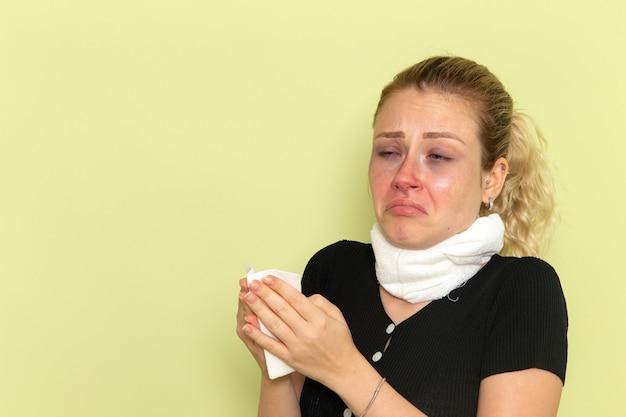 Vooraanzicht jonge vrouw met witte handdoek om haar keel erg ziek en ziek voelen op lichtgroene muur ziekte ziekte vrouwelijke kleur gezondheid