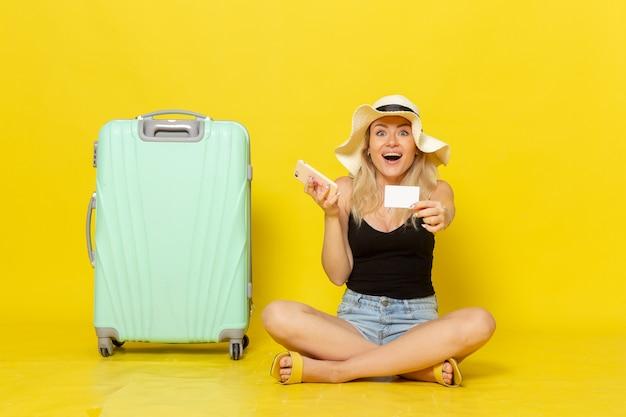 Vooraanzicht jonge vrouw met witte kaart en telefoon