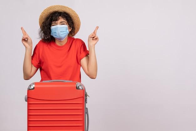 Vooraanzicht jonge vrouw met zak in masker hopend op witte achtergrondkleur covid-pandemische zon virus reis toeristische vakantie