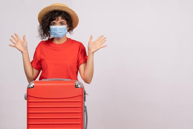 Vooraanzicht jonge vrouw met zak in masker op een witte achtergrond covid-pandemische virusreis toeristische zon vakantie kleur Gratis Foto