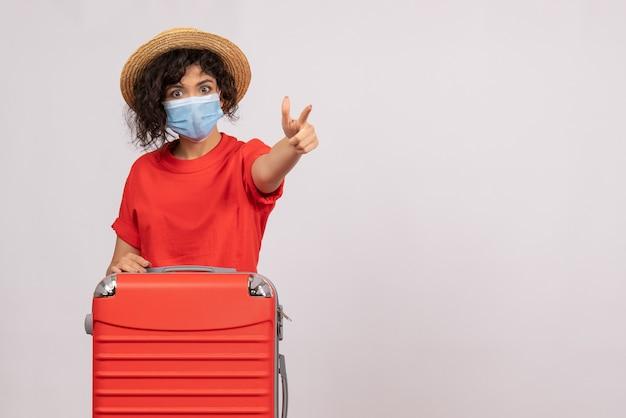 Vooraanzicht jonge vrouw met zak in masker op witte achtergrond kleur virus covid-pandemische vakantie zon toerist