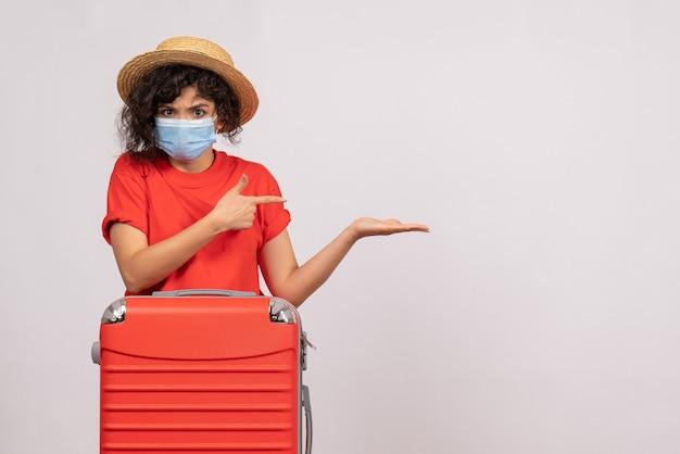 Vooraanzicht jonge vrouw met zak in masker op witte achtergrond kleur virus covid- pandemische vakantiereis zon