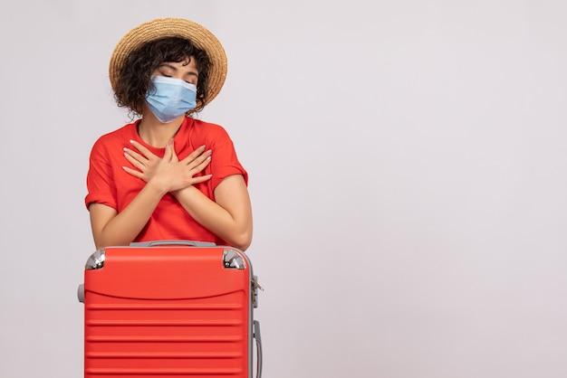Vooraanzicht jonge vrouw met zak in masker op witte achtergrond virus covid-toeristische pandemische vakantie kleur reis