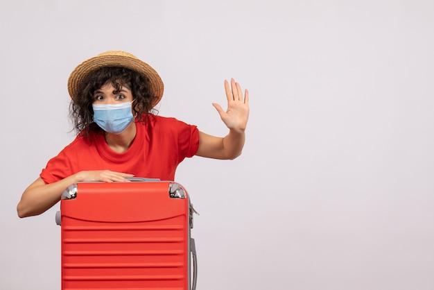 Vooraanzicht jonge vrouw met zak in masker op witte achtergrondkleur covid-vakantie pandemische zon virus reis toerist
