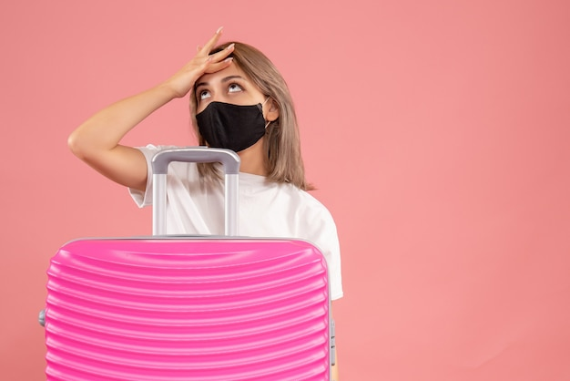Vooraanzicht jonge vrouw met zwart masker die haar hoofd vasthoudt