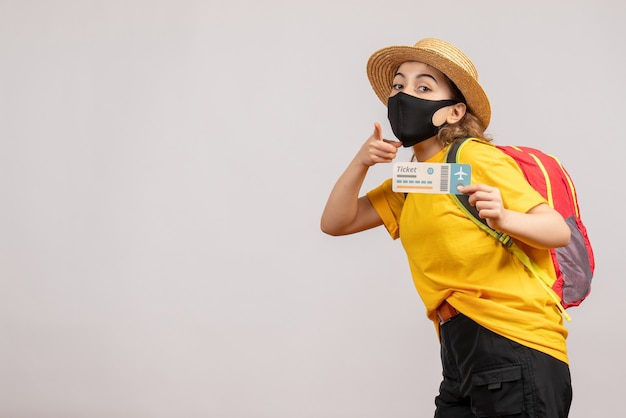 Vooraanzicht jonge vrouw met zwart masker met reiskaartje wijzend naar voren