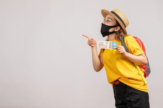 Vooraanzicht jonge vrouw met zwart masker met reiskaartje wijzende vinger naar links