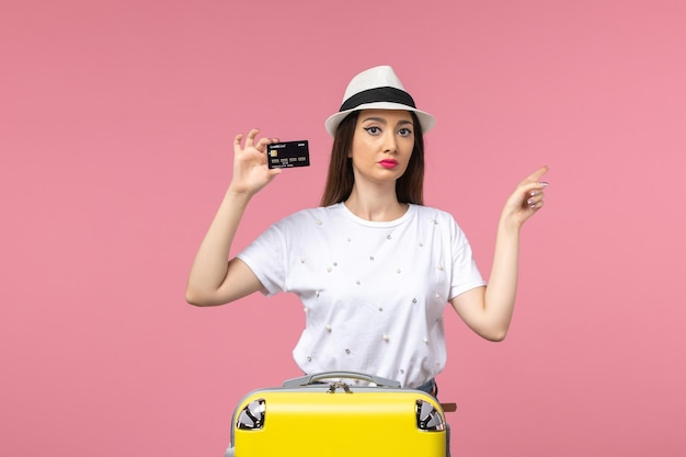 Vooraanzicht jonge vrouw met zwarte bankkaart op de roze muur reis kleur reis zomer
