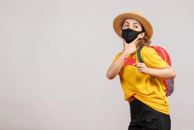 Vooraanzicht jonge vrouw met zwarte masker met kaart die hand op haar kin legt