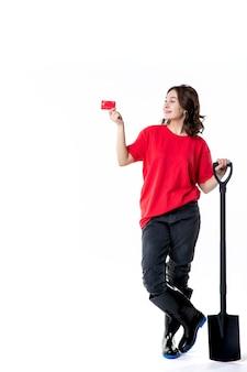 Vooraanzicht jonge vrouw met zwarte schop en bankkaart op witte achtergrond vrouw werk grond graven baan grond nacht kleur geld