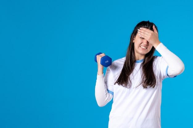 Vooraanzicht jonge vrouw moe van het trainen met halters op blauwe muur