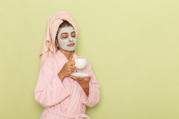 Vooraanzicht jonge vrouw na douche in roze badjas koffie drinken op groene ondergrond