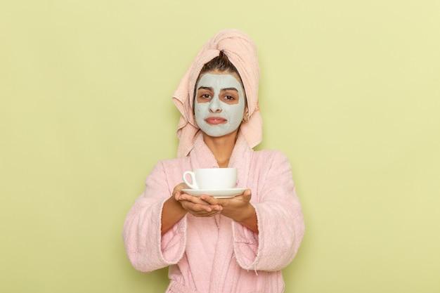 Vooraanzicht jonge vrouw na douche in roze badjas koffie drinken op lichtgroene ondergrond