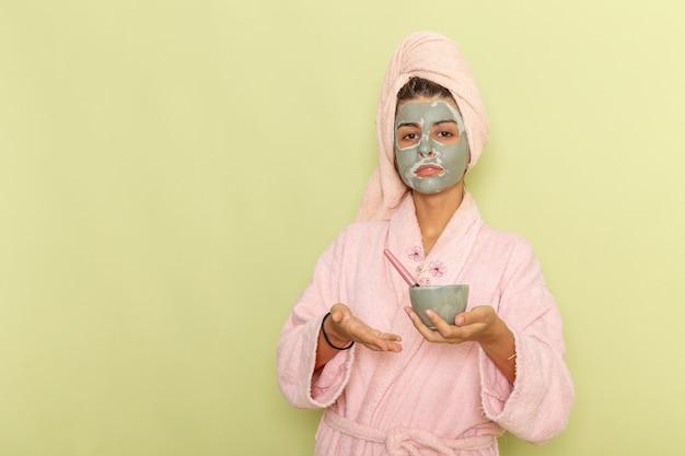 Vooraanzicht jonge vrouw na douche in roze badjas masker toe te passen op een groen oppervlak