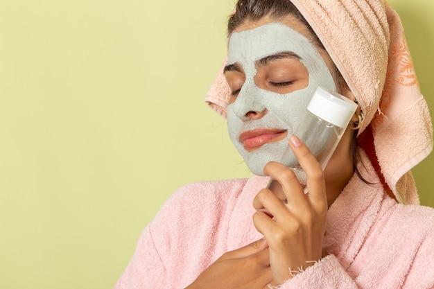 Vooraanzicht jonge vrouw na douche in roze badjas met make-up remover op groen oppervlak