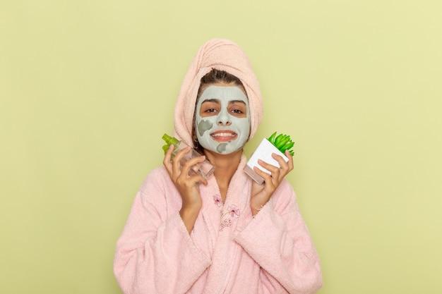 Vooraanzicht jonge vrouw na douche in roze badjas met make-up verwijderaars lachend op groen oppervlak