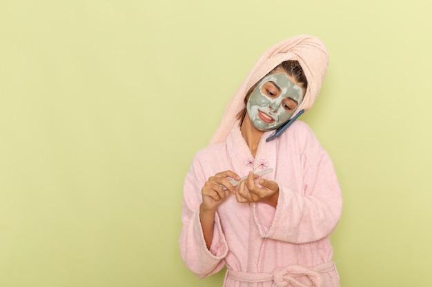 Vooraanzicht jonge vrouw na douche in roze badjas praten aan de telefoon op groen oppervlak